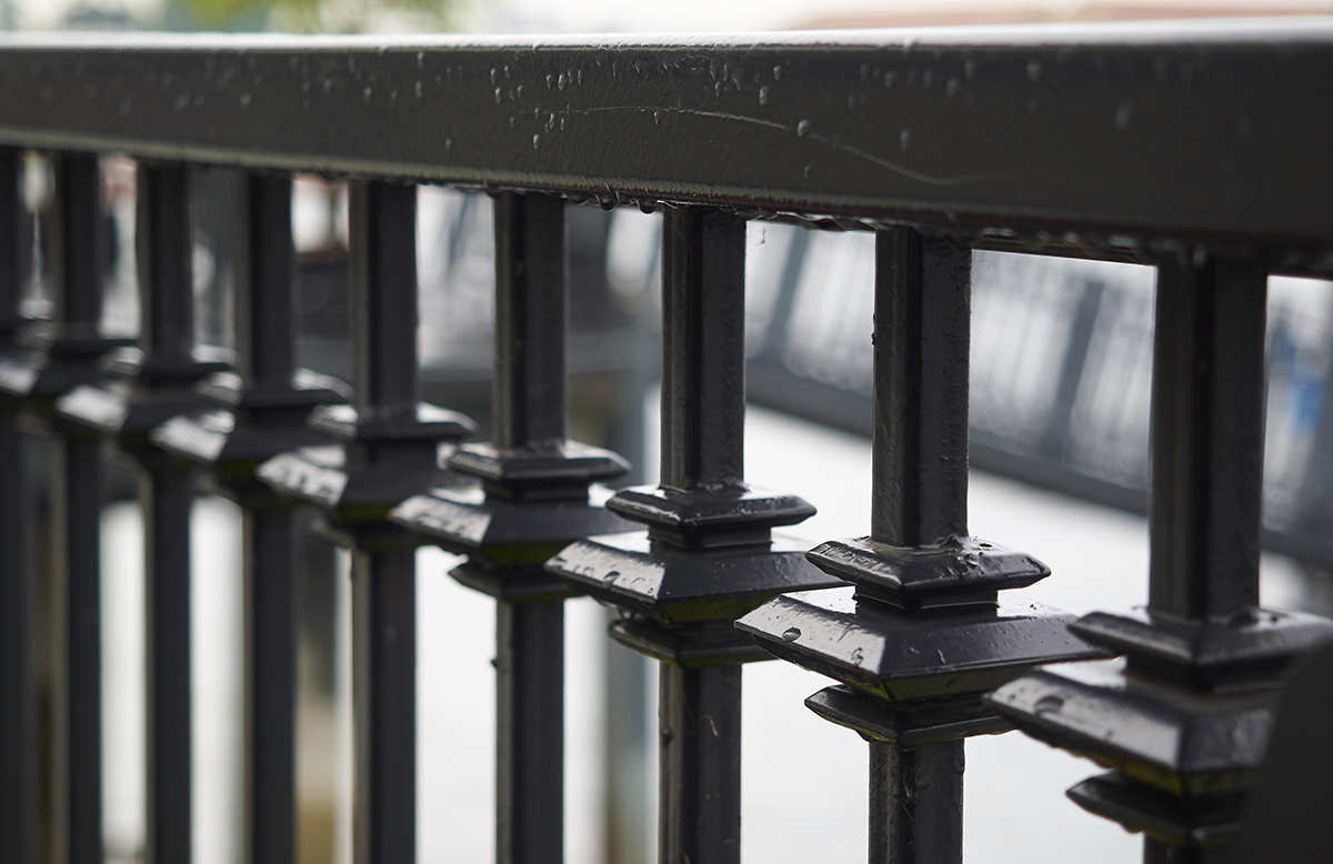 close up line of wrought-iron fence spikes