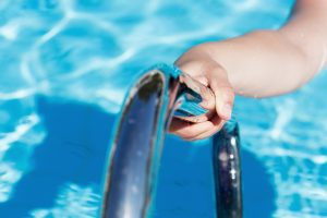 Female's hand holding a handrail in swimming pool